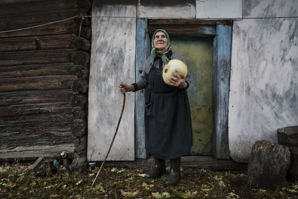 Hanna Zavorotnya 83 years old in front of the pantry of her home with a pumpkin in her arm, Kupovate, Chernobyl Exclusion Zone