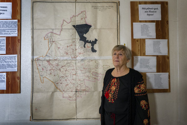 """Nadia Lishilenko director of the Radinka school in front of the map of lands contaminated by Chernobyl. In 2015 the government decided to declassify these provinces from zone 4 to """"clean"""" areas to stop paying compensation to the affected population."""