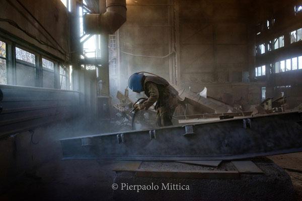 Yuriy mentre pulisce i metalli contaminati con il processo della sabbiatura