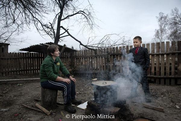 Igor con sua madre mentre prepara la prima colazione. Per il riscaldamento e la cottura la popolazione locale brucia legna presa all'interno della zona di esclusione di Chernobyl e dalle zone circostanti, legna altamente radioattiva.