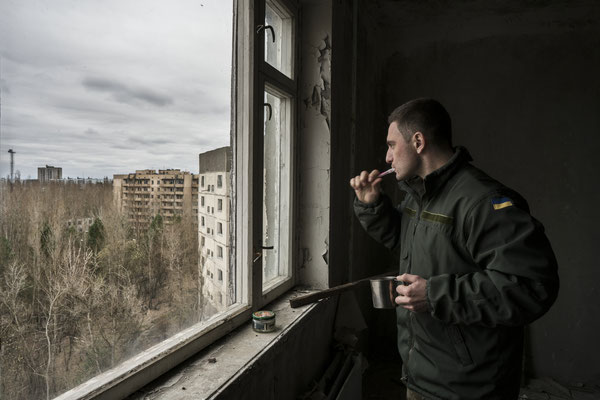 Maxim brushing his teeth in Jimmy's apartment, looking at the landscape of the ghost town of Pripyat.