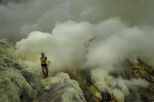 a miner while collecting chunks of sulphur in the volcano crater
