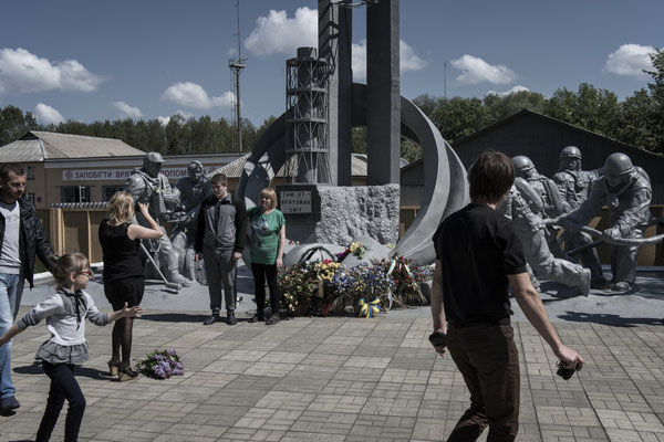 Former residents of the area with their families taking souvenir photos in front of the memorial to the Chernobyl firefighters. Chernobyl city.