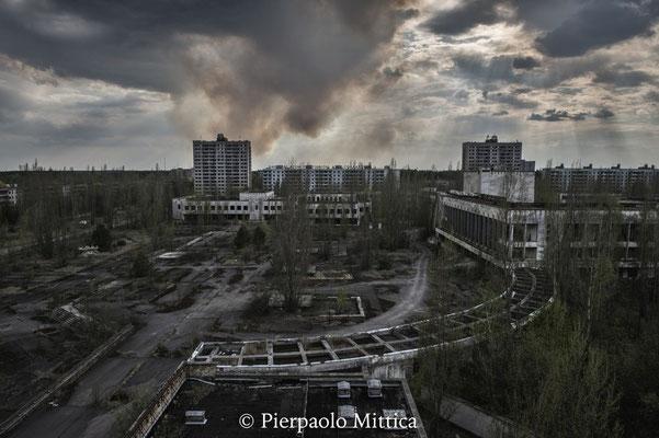 la foresta brucia dietro la città fantasma di Pripyat. Uno dei maggiori pericoli esistenti nella zona di esclusione sono gli incendi. Il fuoco brucia gli alberi e la cenere radioattiva viene sparsa nell'aria, provocando un nuovo fallout nucleare.