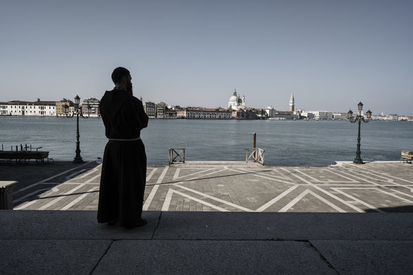 A friar looks at the empty square in front of the Redentore church