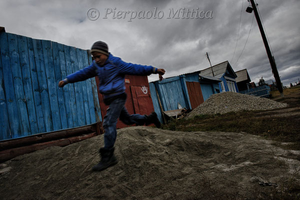 Child playing in the contaminated village of Karabolka