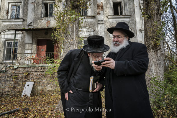 Yitz Twersky in front of the former synagogue while showing some old pictures of the Synagogue to Rabbi Leibel Sirkes