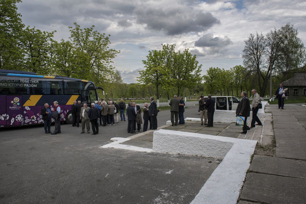 Former exclusion zone inhabitants in the main square of the city of Chernobyl as they wait to board the bus to exit the exclusion zone after their visit.