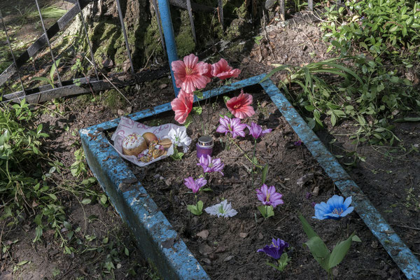 a tomb with flowers and ornaments in the Chernobyl cemetery