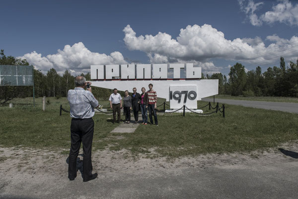 Former inhabitants of the city of Pripyat taking a souvenir photo in front of the city stele.
