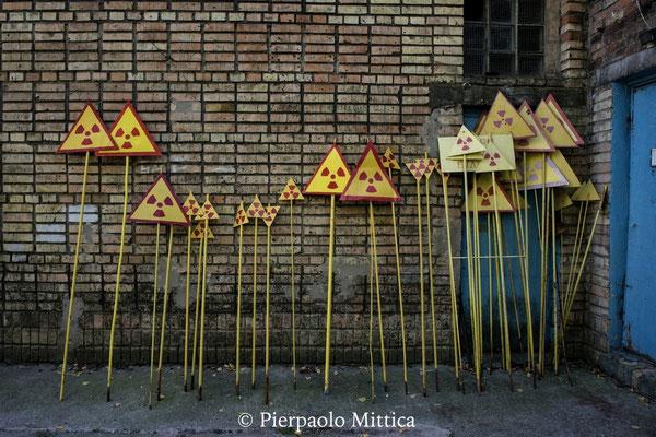 Nella città fantasma di Pripyat, c'è una rimessa dove vengono dipinti i cartelli di pericolo di radiazioni consumati dal tempo e dalle intemperie. I nuovi cartelli sono pronti per essere piantati nella zona per segnalare i luoghi più contaminati