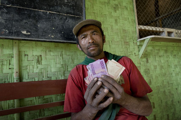 Marsugi, lives in Panggang village, showing the wage he has just got from his day shift, 6 euros