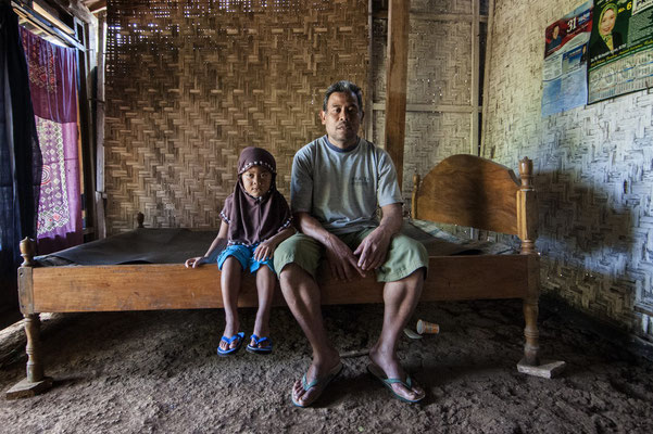 Usni with his grand daughter at home, he lives in Sumberwatu village