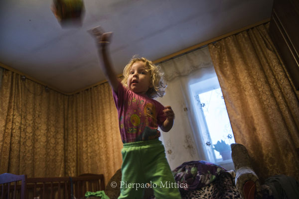 Victoria, 3 yo, playing at home. She's the daughter of Victor, the manager of the site where radioactive metal is recycled.  The whole family lives in the village of Kovalivka, located at 5 km from the Chernobyl Exclusion Zone