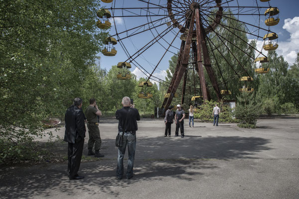 Former inhabitants of the city of Pripyat taking souvenir photos in front of the city ferris wheel.