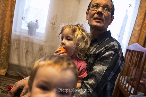 Victor con i suoi due figli, Alexander di 1 anno e Victoria di 3 anni nella sua casa a Kovalinka