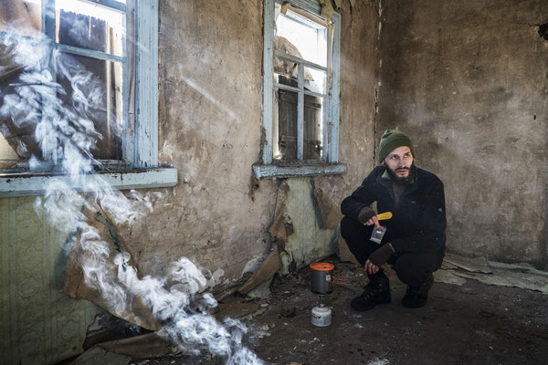 Jimmy preparing breakfast in the abandoned village of Rudnya Veresnya, inside the Zone of exclusion. The village is located 20 km after the border of of the Zone, and it's the first stop of the stalkers on their way to Pripyat.