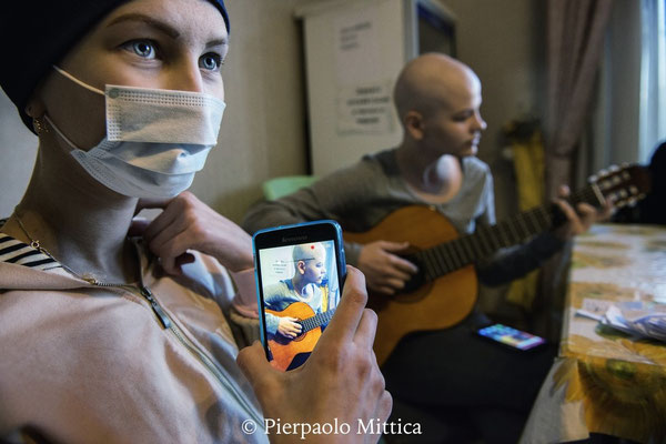 """Olia, 14 anni è affetta da osteosarcoma. Qui sta filmando la sua amica Ania mentre suona la chitarra. Ania soffre di un cancro alla tiroide e alle ovaie. Casa famiglia dell'associazione """"Zaporuka"""", Kiev"""