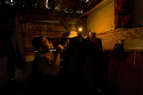 Imik, lives in Glondak village, here he is smoking and resting in the dimmed room before leaving for his night shift