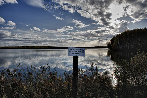Contaminated lake used to discharge plutonium from the nuclear power plant. The sign warns: forbidden area, forbidden access. near Novogorny