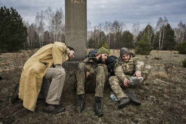 Sasha, Jimmy and Maxim during a pause of their journey to Pripyat while checking their feet filled with blisters for their long walk.