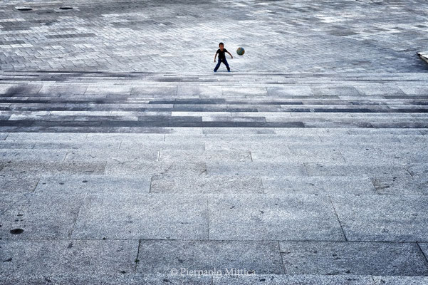 A child playing football in an empty square