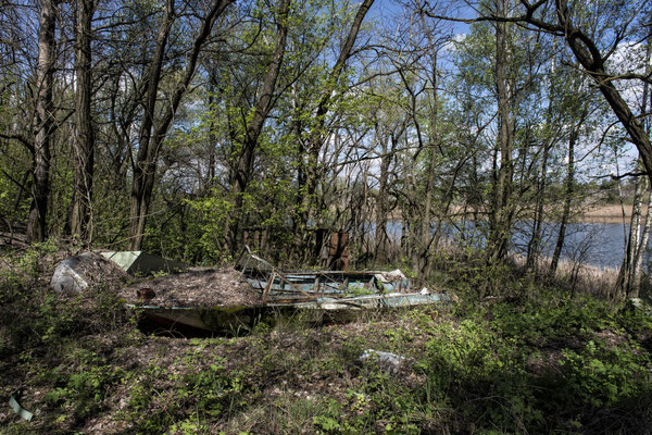 An abandoned boat wrapped in nature in the Yacht club of the ghost town of Pripyat.