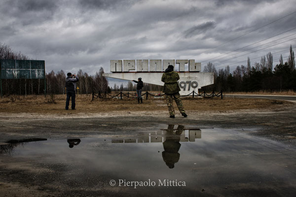 Tourists while photographing in front of the stele of Pripyat, exclusion zone