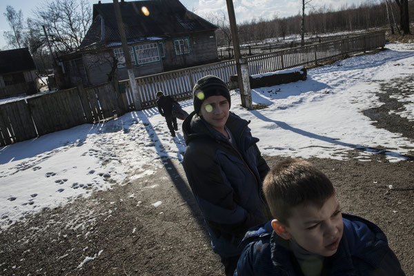 Igor, Vladik and Viktor in front of their home in Radinka waiting to go to the hospital in Ivankiv for analysis
