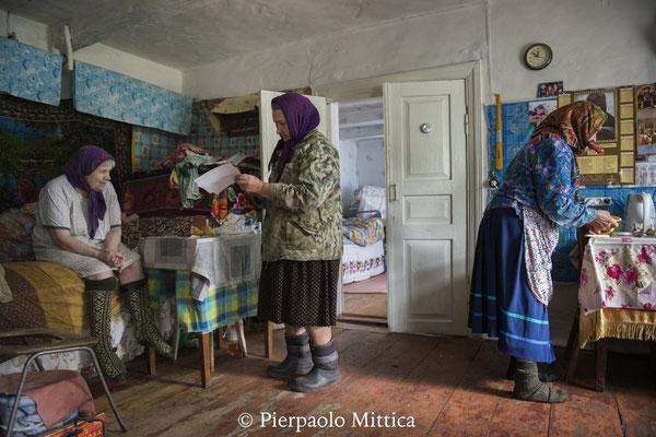 Hanna con Maria e sua sorella Sofia nella sua casa mentre prepara i funghi appena raccolti per il pranzo, villaggio di Kupovate, zona di esclusione di Chernobyl