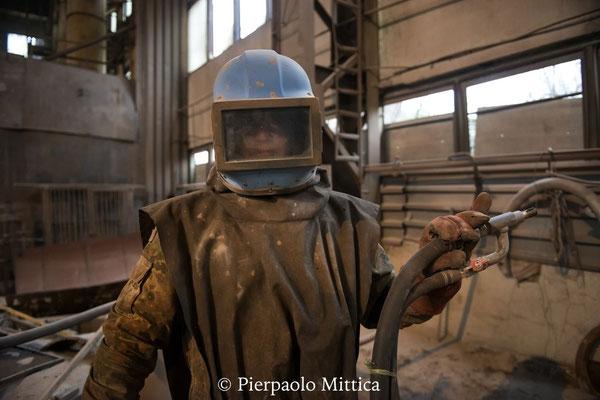 Yuriy con la tuta di protezione per la sabbiatura dei metalli radioattivi per il loro riciclo