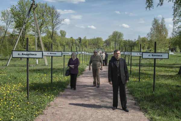 Former inhabitants strolling in the main square of the city of Chernobyl where the monument was erected in memory of the towns abandoned due to the accident. Chernobyl city.