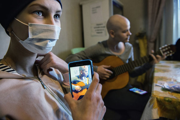 Olia, 14 years old is affected by an osteosarcoma. Here she is filming her friend Ania playing guitar. Ania suffers from a thyroid and ovaius cancer. family home, Kiev.