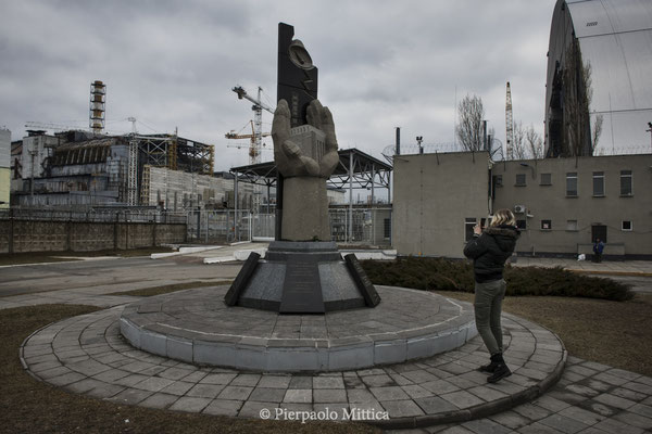 a Tourist in front of sarcophagus of reactor number four, Chernobyl nuclear power plant