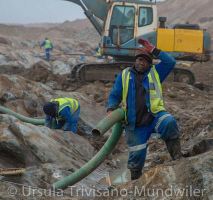 Diamantminenarbeiter beim Absaugen des Diamantschlamms
