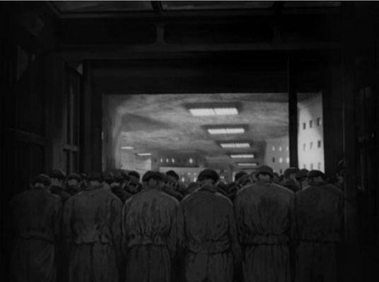 die ausgebeuteten Arbeitermassen auf Weg zurück in ihre triste, unterirdische Heimat. Sie sind uniform in Kleidung und Bewegung und verschwimmen zu einer anonymen Masse
