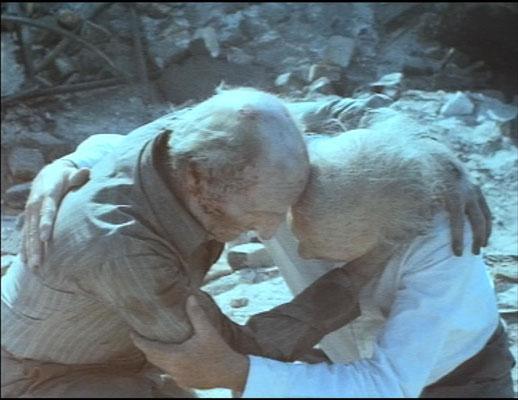 ein Bild sagt mehr als tausend Worte: Dr. Oakes wird in seinem zerstörten Haus von einem Fremden getröstet. Beide sind schwer von der Strahlenkrankheit gezeichnet
