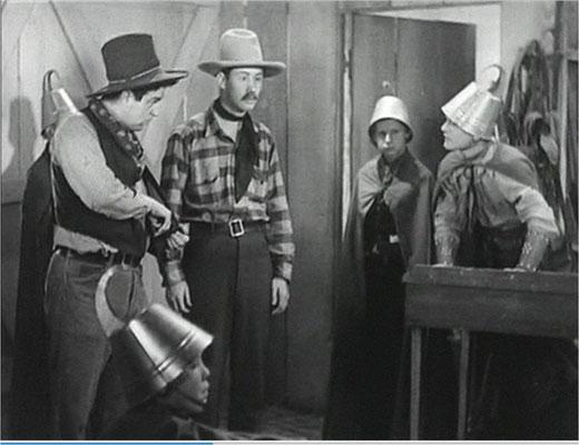 es sind tatsächlich Blecheimer, was diese Kinder auf dem Kopf tragen. Hier eine Szene mit Frankie Darro, am Tisch, und dem aus dem Slapstick bekannten Smiley Burnett, links