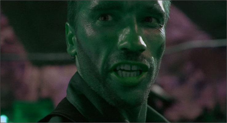 """Arnold Schwarzenegger bat die Drehbuchautoren, nach harten Actionszenen hin und wieder etwas Humur einfließen zu lassen. Sprüche wie das hier gesagte """"Stick around"""", nachdem er einen Feind mit einer Machete an eine Wand gespießt hat, wurden eine Art Marke"""