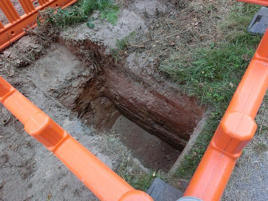 Eine abgesperrte Inspektions-Grube, eine Baggerschaufel breit