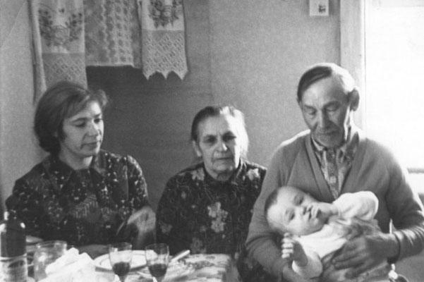 Я с мамой, бабушкой и дедушкой внутри дома в первой комнате (в доме было 2 комнаты, эта первая, при входе попадали сначала в неё, потом во вторую, которая на предыдущем фото с печками), наверху стояла икона, в том месте где на стене видна свисающая матери