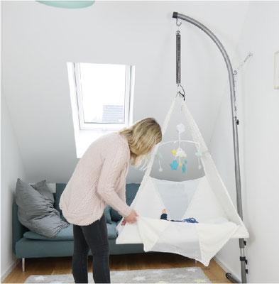 Mama legt ihr Kind in Federwiege, Entspannung für Eltern und Baby, natürlicher Schlaf für Neugeborene