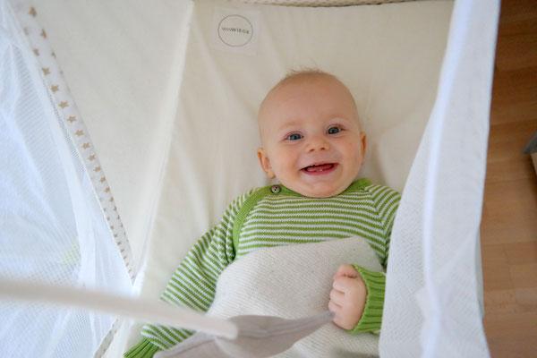 Lachendes Baby in Federwiege, Reisebett,