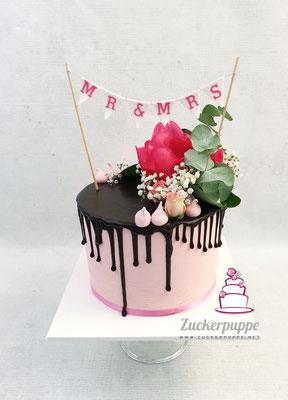 Dripcake mit frischen Blüten und handgemachter Wimpelkette zur Hochzeit von Stephanie und Raoul