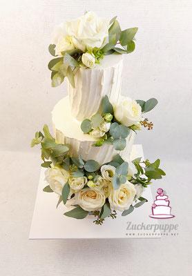 geschwungene Buttercremelinien mit weissen Rosen und Eukalyptus zur Hochzeit von Kathrin und Jonas