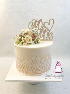 Zarter Goldschimmer und Zuckerspitze mit frischen Blumen zur Hochzeit von Ladina und Luigj