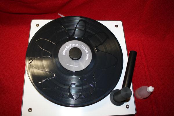 Der Plattenteller wird eingeschaltet und durch eine Vorwärts- und Rückwärts-Bewegung der Dosierflasche wird die Flüssigkeit dabei wellenförmig aufgebracht