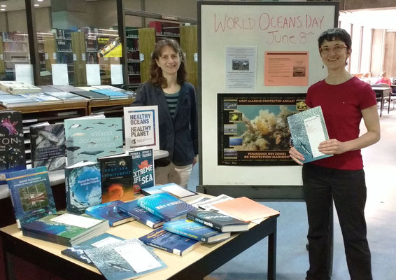IOI CANADA:  Book display - Librarian Michelle Paon holding a copy of one of the World Ocean Reviews, together with the IOI Programme Officer, Madeleine Coffen-Smout