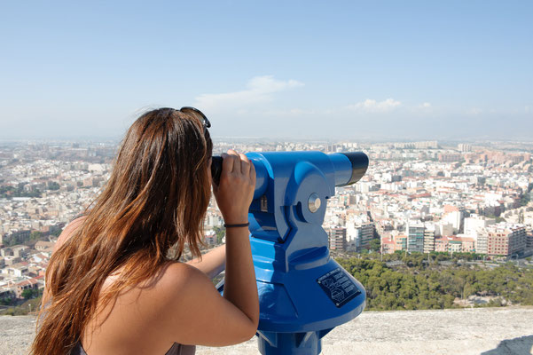 Tourist looking at cityscape on the top of castle tower, Santa Barbara, Alicante, Spain by Borja Laria