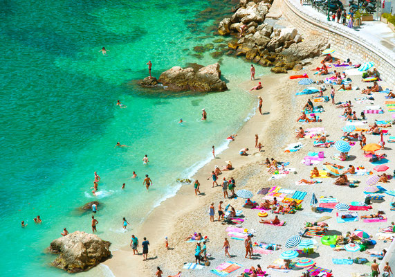beach of the Cote d'Azur with tourists with sunbeds and umbrellas on the hot summer day Copyright LiliGraphie